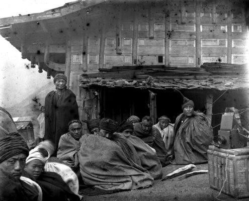 Familiengruppe vor einem Haus der Yi mit typischer Kleidung und Kopfschmuck, Herbst 1913